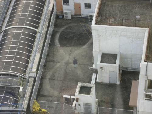 センタープラザの向かいのビルの屋上を8の字に歩くおじさん