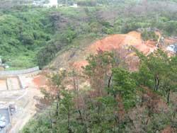 山を削って、赤土をトラックで運び出しています