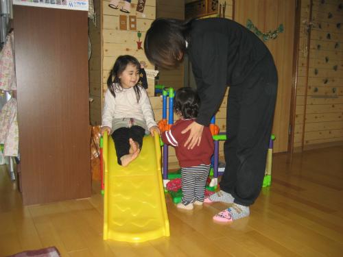 クレアちゃんが翔瑛ちゃんに滑り台の使い方を見せています
