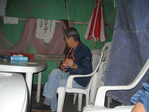 上間雄明さんが、三線を物置から取り出して、弾いています