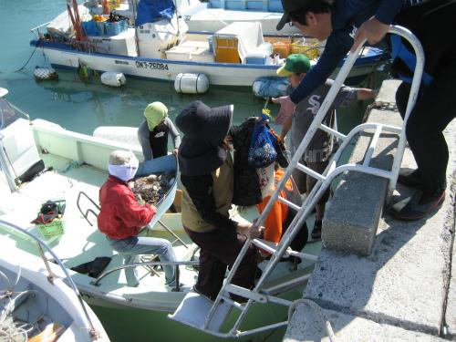獲った魚や貝などを、船から港に上げていきます
