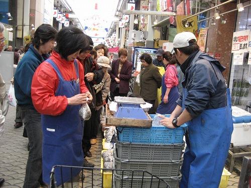 魚の棚のお店の前で売られる「いかなご」に人が集まっています